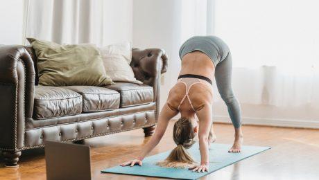 unrecognizable woman in sportswear doing yoga near laptop in apartment